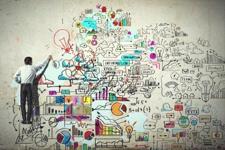 Photo pour Back view of businessman drawing sketch on wall - image libre de droit
