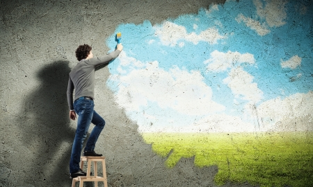 Photo pour Young man drawing a cloudy blue sky on the wall - image libre de droit
