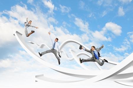 Foto de Young businesspeople jumping on white arrows  Growth concept - Imagen libre de derechos