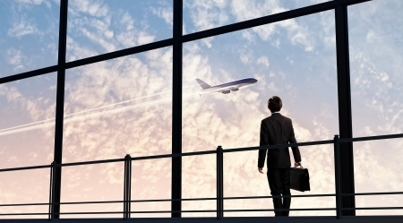Photo pour Image of businessman at airport looking at airplane taking off - image libre de droit