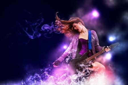 Foto de Young attractive rock girl playing the electric guitar - Imagen libre de derechos