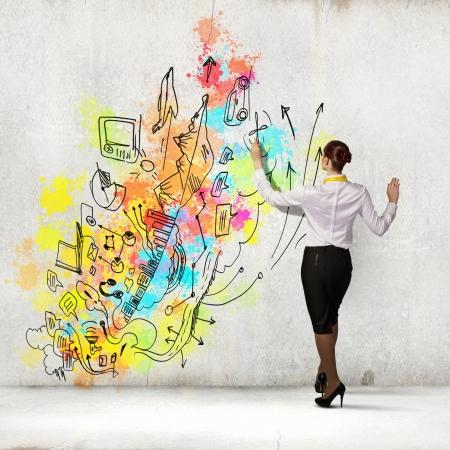 Foto de Back view of businesswoman drawing colorful business ideas on wall - Imagen libre de derechos