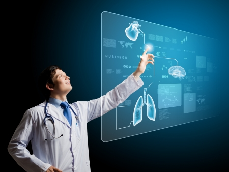 Foto per Young male doctor touching icon on media screen - Immagine Royalty Free