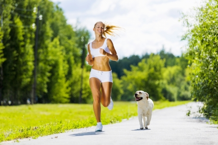 Photo pour Young attractive sport girl running with dog in park - image libre de droit