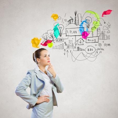 Foto de Image of thoughtful businesswoman with business sketch at background - Imagen libre de derechos