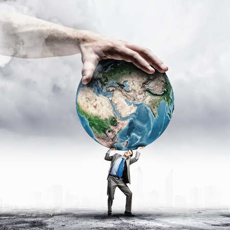Foto de Image of young businessman under pressure of planet Earth  Elements of this image are furnished by NASA - Imagen libre de derechos