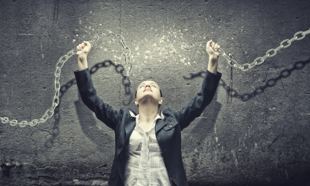 Foto de Image of businesswoman in anger breaking metal chain - Imagen libre de derechos
