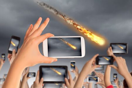Photo pour People taking photos of falling meteorite on mobile phone camera - image libre de droit