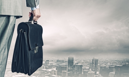 Photo for Back view of businessman with suitcase looking at city - Royalty Free Image