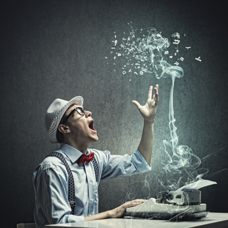 Photo pour Young funny man in glasses writing on typewriter - image libre de droit