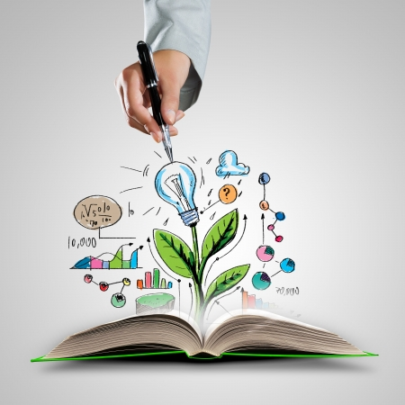 Foto de Opened book with business sketches and hand holding pen - Imagen libre de derechos
