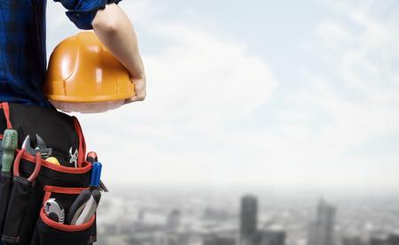 Photo pour Close up of woman mechanic with yellow helmet in hand against city background - image libre de droit