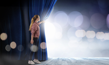 Photo for Young woman in casual opening blue curtain - Royalty Free Image