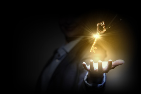 Photo pour Close up image of business person holding shining key - image libre de droit