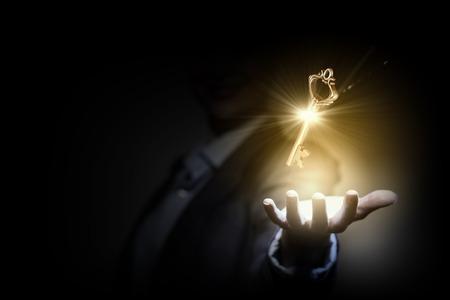 Foto de Close up image of business person holding shining key - Imagen libre de derechos