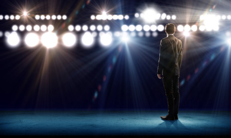 Photo for Rear view of businessman standing in lights of stage - Royalty Free Image