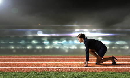 Photo pour Side view of businesswoman at stadium standing in start position - image libre de droit