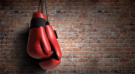 Photo pour Pair of red boxing gloves hanging on wall - image libre de droit