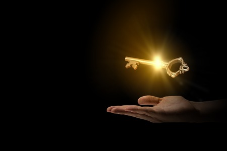 Foto de Close up of human hand holding golden key - Imagen libre de derechos