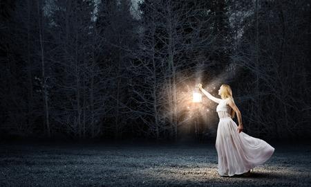 Foto de Young woman with lantern walking in dark forest - Imagen libre de derechos