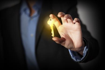 Foto de Close up of human hand catching golden key - Imagen libre de derechos