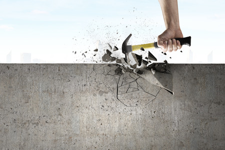 Photo pour Close up of hammer in hand breaking cement wall - image libre de droit
