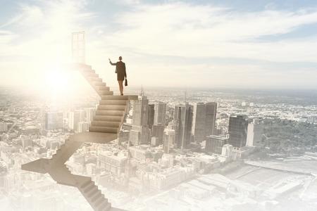 Photo pour Businesswoman walking up staircase to door in sky - image libre de droit
