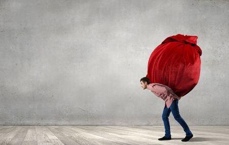Foto de Young man in casual carrying heavy red bag - Imagen libre de derechos