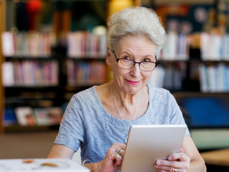 Photo pour Elderly lady working with tablet - image libre de droit
