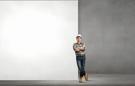 Photo pour Young builder man leaning on white blank banner. Place for text - image libre de droit