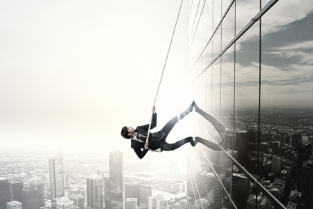Foto de Concept of competition with businessman climbing office building with rope - Imagen libre de derechos