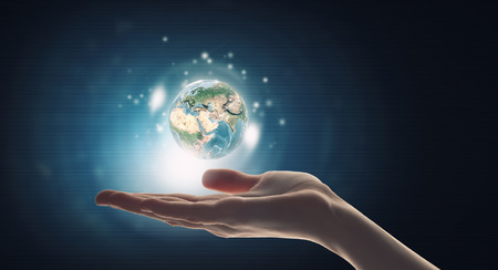 Photo pour Human hand holding digital icon of planet earth.  - image libre de droit