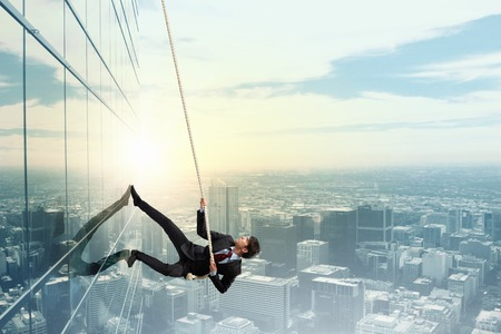 Photo pour Concept of competition with businessman climbing office building with rope - image libre de droit