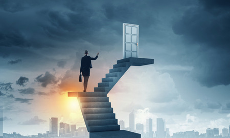 Photo pour Businesswoman walking up staircase to door in sky - image libre de droit