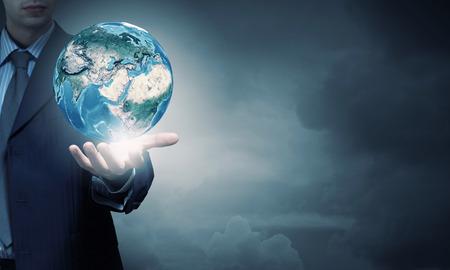 Photo pour Hand of businessman holding earth planet. - image libre de droit