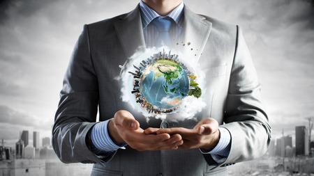 Foto de Young businessman holding Earth planet in hand.  - Imagen libre de derechos