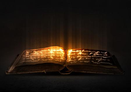 Photo pour Old black magic book with lights on pages - image libre de droit