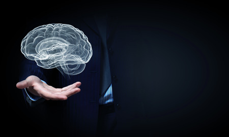 Foto de Close up of businessman hand holding brain in palm - Imagen libre de derechos