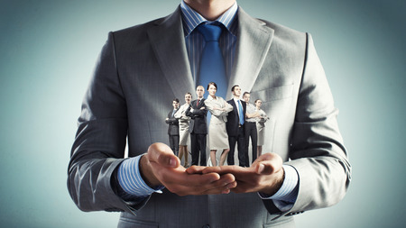 Photo pour Close up of businessman holding in hands successful business team - image libre de droit