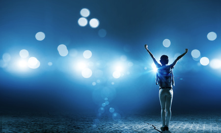 Photo for Back view of girl standing in stage lights - Royalty Free Image
