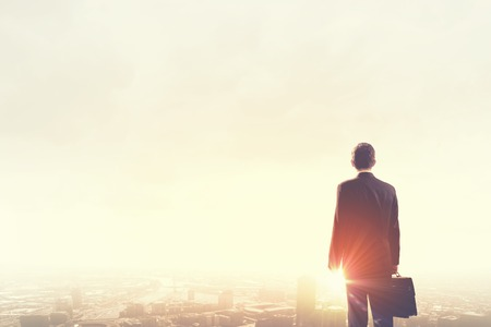 Photo for Rear view of businessman looking at sunset above city - Royalty Free Image