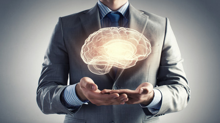 Foto de Close up of businessman holding digital image of brain in palm - Imagen libre de derechos