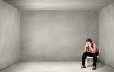 Foto de Depressed man sitting on a chair all alone - Imagen libre de derechos