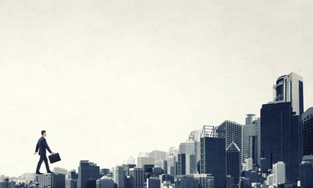 Foto de Young businessman walking on buildings roofs representing success concept - Imagen libre de derechos