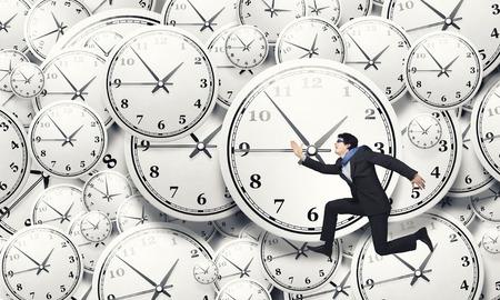 Foto de Concept of time with funny businessman running in a hurry - Imagen libre de derechos