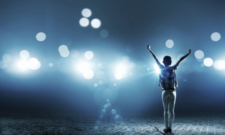 Photo for Back view of girl with hands up standing in stage lights - Royalty Free Image