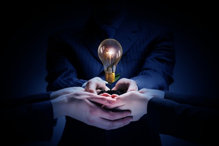Foto per Brainstorming and teamwork concept with diverse business people holding light bulb in hands - Immagine Royalty Free