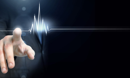 Foto de Male hand touch heart pulse on futuristic interface - Imagen libre de derechos