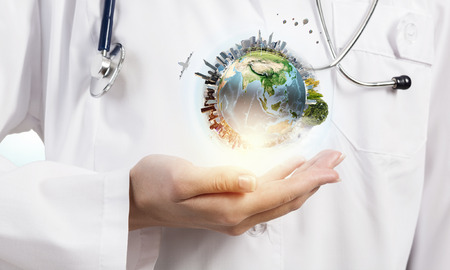 Foto per Close up of female doctor holding Earth planet in hands. Elements of this image are furnished by NASA - Immagine Royalty Free