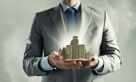 Photo pour Close up of businessman holding modern office center model in hands - image libre de droit